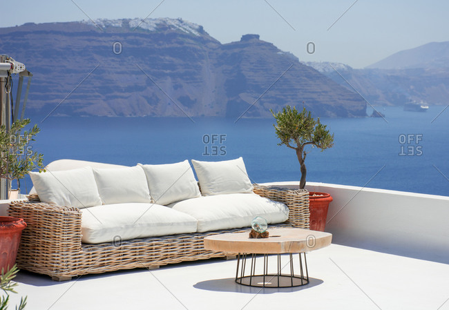 beautiful terrace with couch and a small table in the village of Oia in the greek island of Santorini. Nobody is enjoying now the spectacular panoramic to the cliff with Fira at the top. Hori