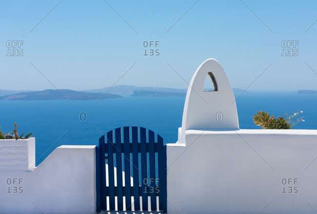 Facade of brick fence or small white wall with a blue gate to enter or exit and a white chimney without smoke with the blue Aegean sea at the back in the idyllic island of Santorini in Greece