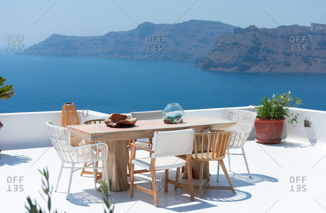 Furniture composed by a table and some chairs on a white terrace of a house in Santorini Greece where you can enjoy meal while seeing a romantic seascape to the blue Aegean sea. Horizontal ph