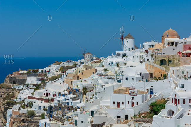amazing panoramic view of some white houses of the village of touristic Oia in Santorini island in Aegean sea. The windmill is at the top of the village and the sea at the background. Horizon
