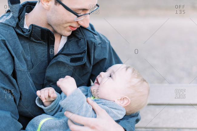 A father holding his baby boy during a break from a hike.