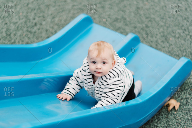 Little baby boy climbing up a blue plastic slide on the playground.