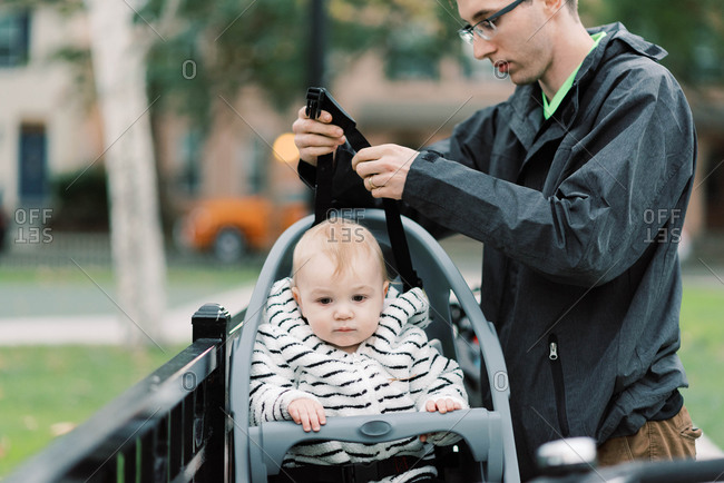 A young millennial dad strapping his son in his bike seat.