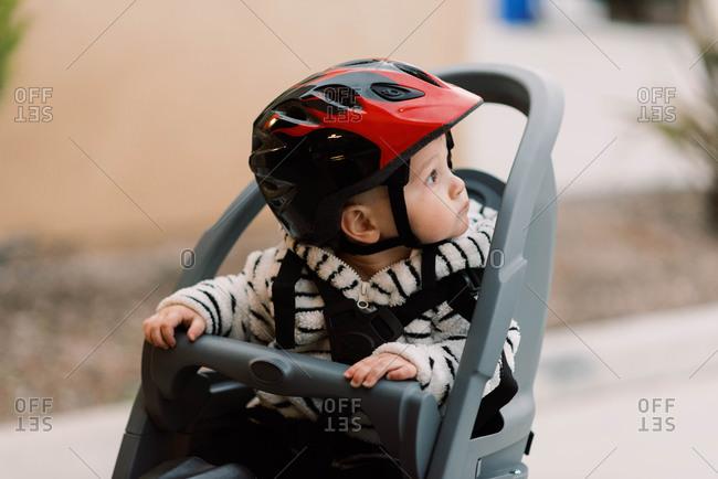 A little baby boy sitting in his bike seat.