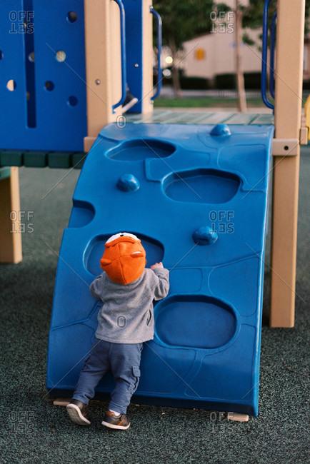 Little boy at the playground wearing a bright orange fox-design hat.