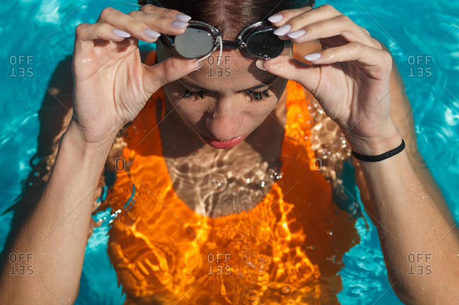 female swimmer in orange swimsuit taking off goggles in swimming pool
