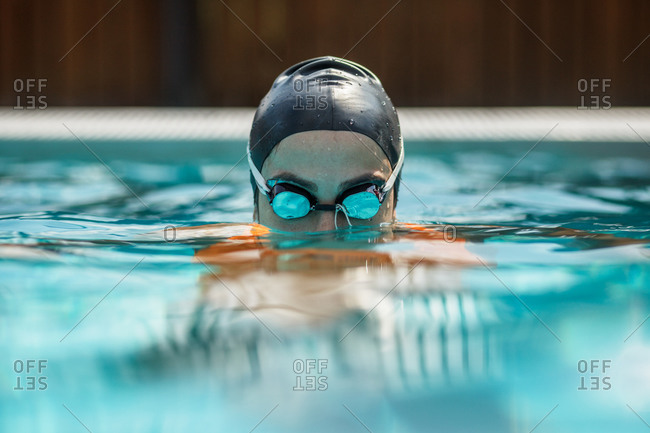 close up of female swimmer in cap and goggles in swimming pool