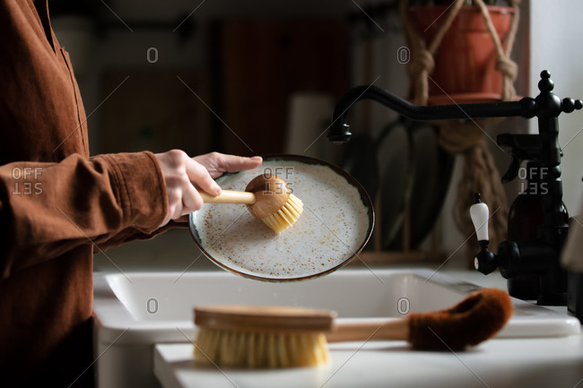 woman washes a plate in the kitchen using eco-friendly brushes