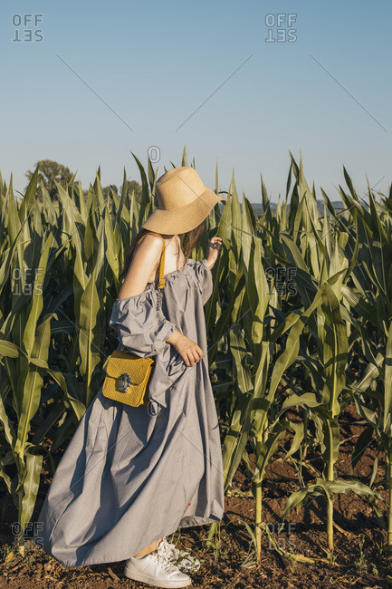 Young girl in light blue linen dress, with a hat and yellow handbag in the corn field