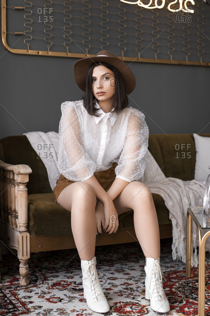 Fashionable young girl with the hat sitting on the couch