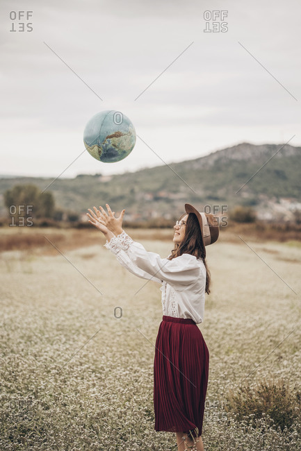 Girl in the field playing with the globe