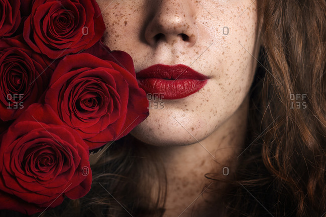 Ginger girl with red lips portrait with red roses