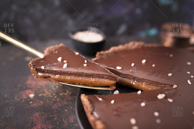 Serving a cuted slice of a salted caramel and chocolate tart