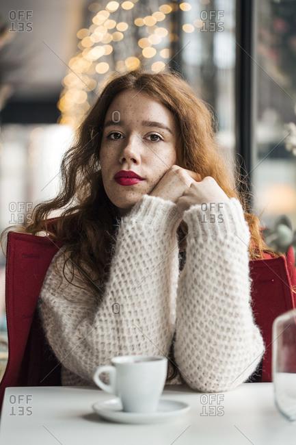 Ginger girl in cafe posing