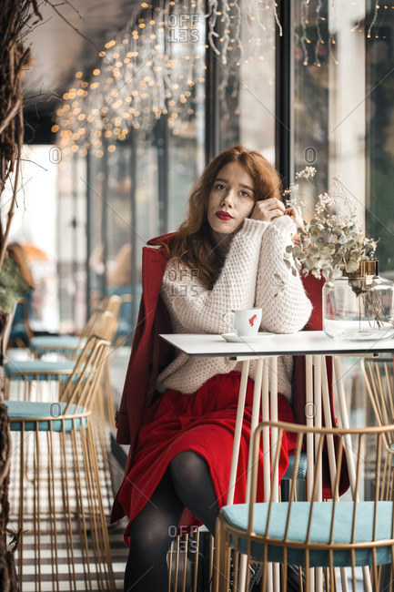 Ginger girl sitting in the cafe in red coat