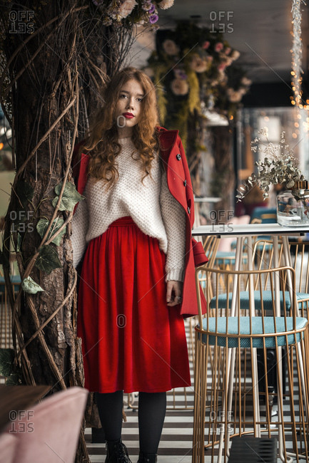 Ginger girl in red dress and coat standing in cafe
