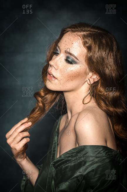 Beautiful ginger girl with freckles posing in studio
