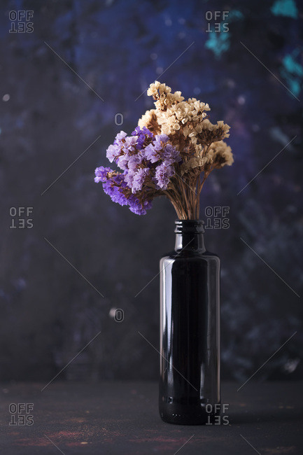 Still life with spring blossoms in black glass bottle