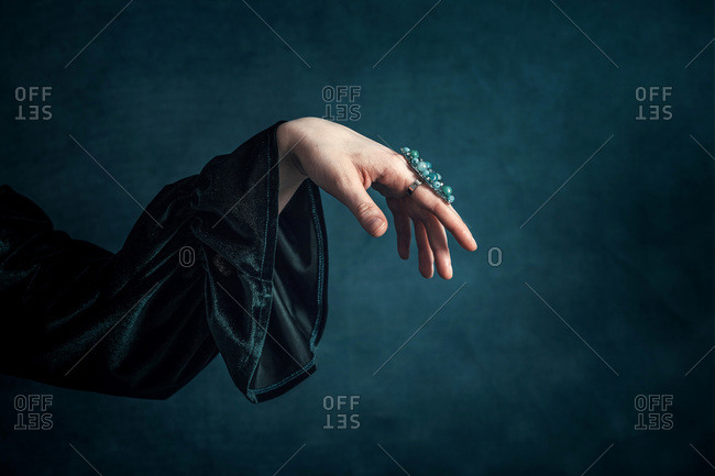 Woman's hand in turquoise dress with turquoise background showing ring