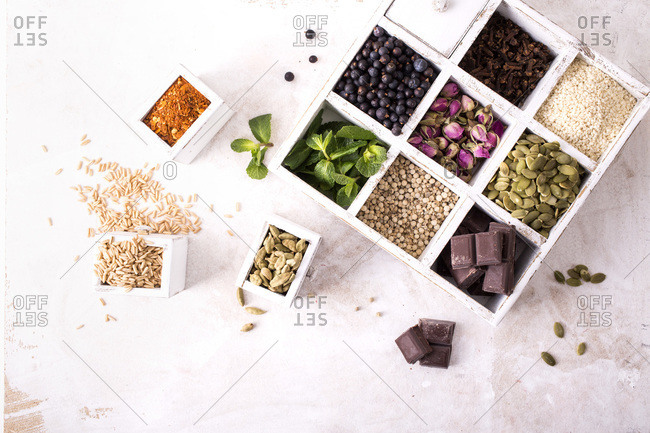 From above set of white wooden containers with assorted dried spices