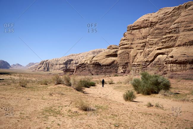 Lonely man walking among the huge rocks in Wadi Rum desert, Jordan