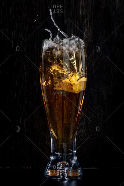 Lemon splashing into a glass of beer