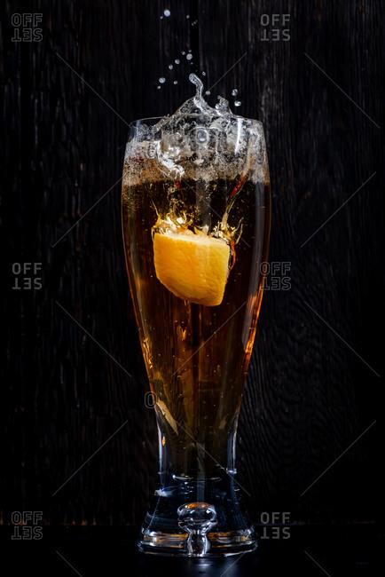 Lemon splashing into a glass of beer on black background