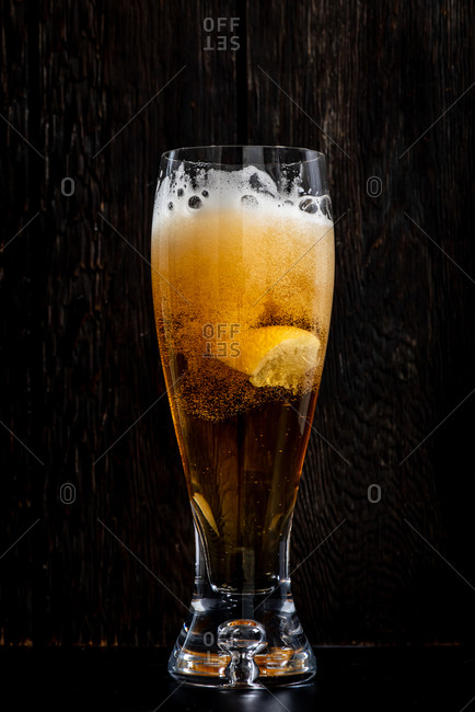 Lemon splashing into a foamy glass of beer on black background