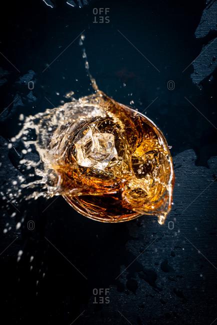 Ice splashing into a glass of bourbon