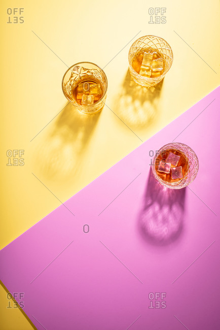 Glasses of bourbon on bright yellow and pink background
