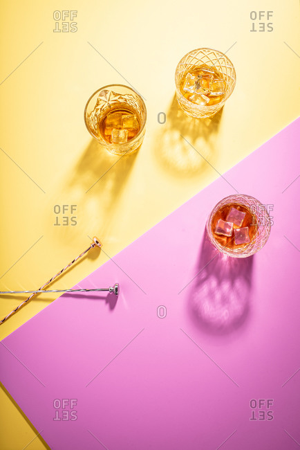 Glasses of bourbon on bright yellow and pink background with stir sticks