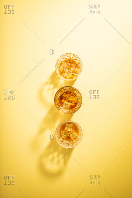 Glasses of bourbon on bright yellow background