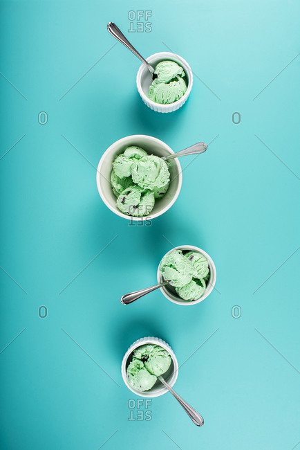 Mint chocolate chip ice cream in dishes on blue background