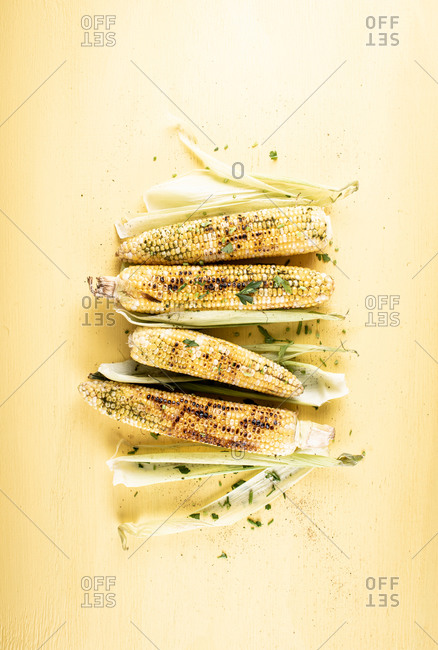 Grilled corn on the cob on yellow background