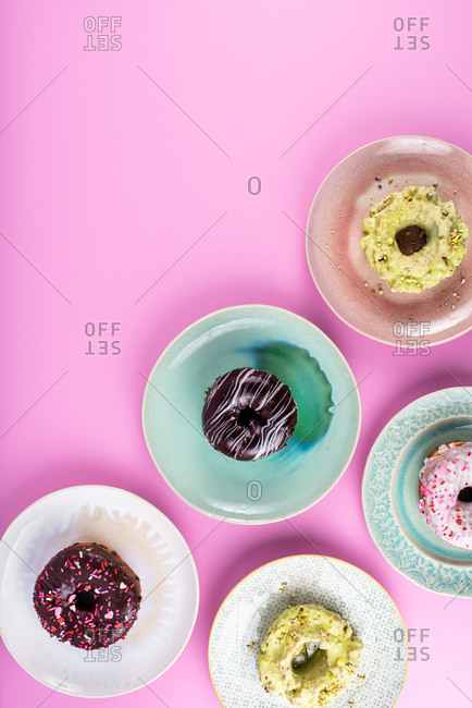 Overhead view of delicious doughnuts on pink background