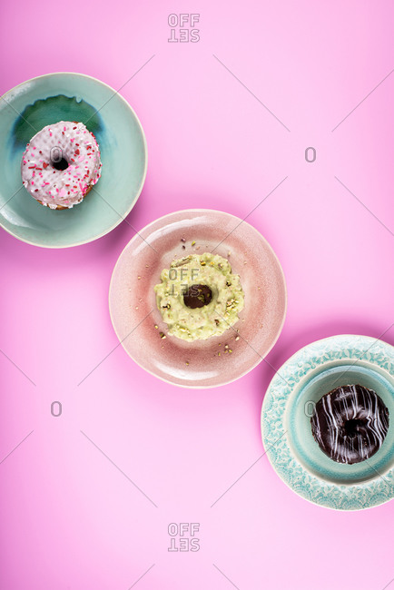 Overhead view of three delicious doughnuts on pink background