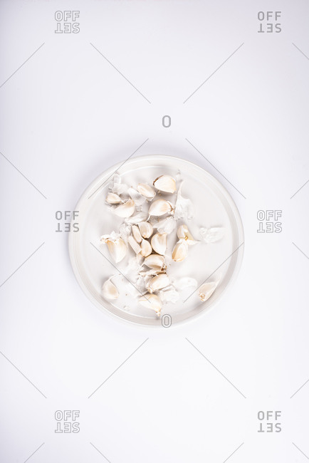 Garlic cloves on a white plate