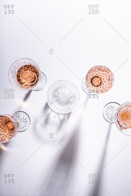Rose wine in glasses on white surface