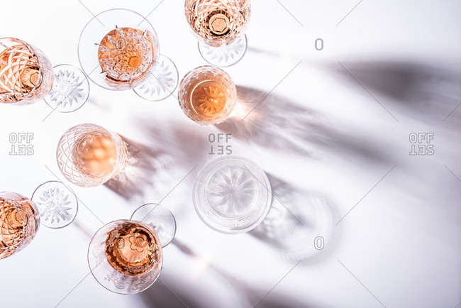 Overhead view of rose wine in glasses on white surface