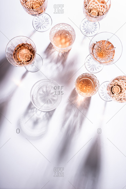 Top view of rose wine in glasses on white surface