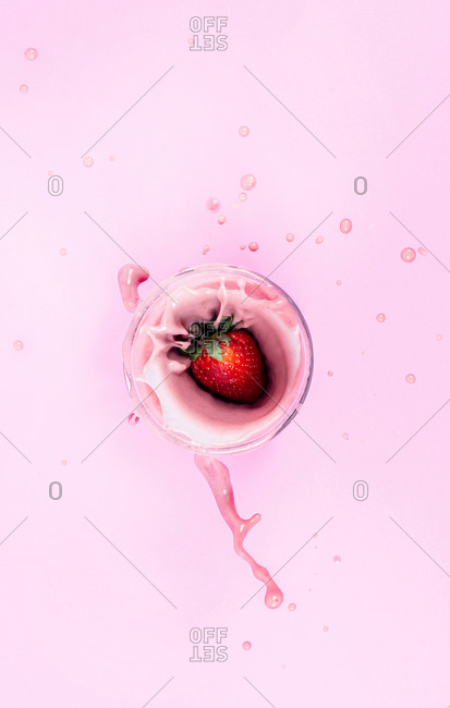 Strawberry splashing into a pink smoothie
