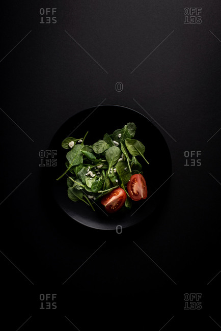 Spinach salad with tomato on a black plate on black background