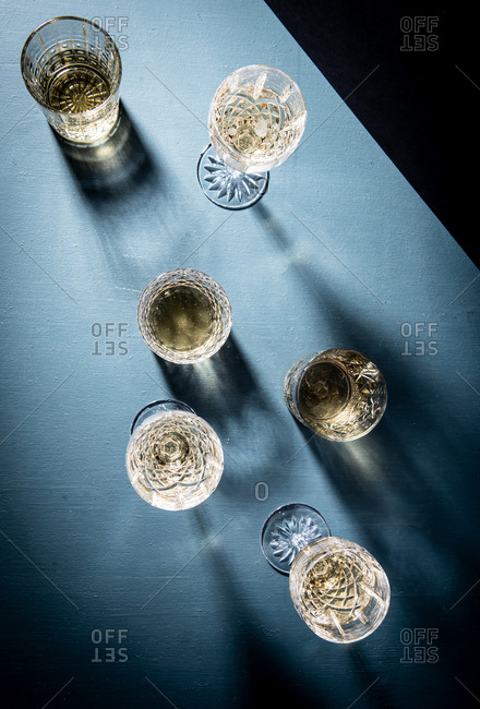 White wine in glasses on blue background