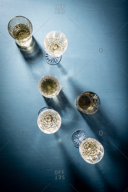 White wine served in glasses on blue background