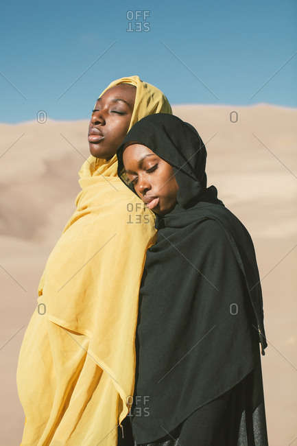 Two young Muslim woman leaning on each other