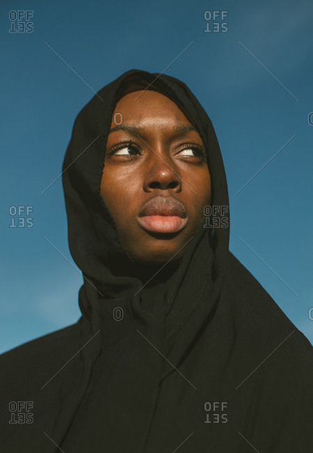 Young Muslim woman dressed in all black looking away