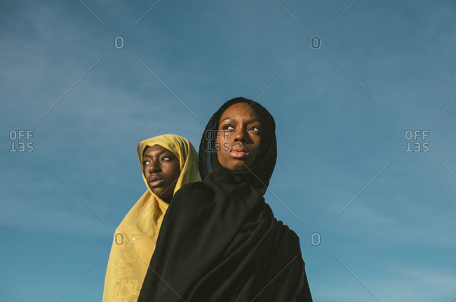 Two young Muslim woman wearing hijabs in front of blue sky