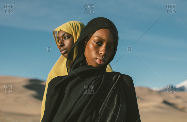 Two young African American Muslim woman wearing hijabs in front of blue sky