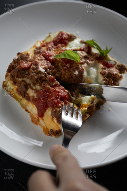 Hands cutting into lasagna on white plate