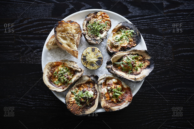 Grilled oysters on a dark surface with lemon
